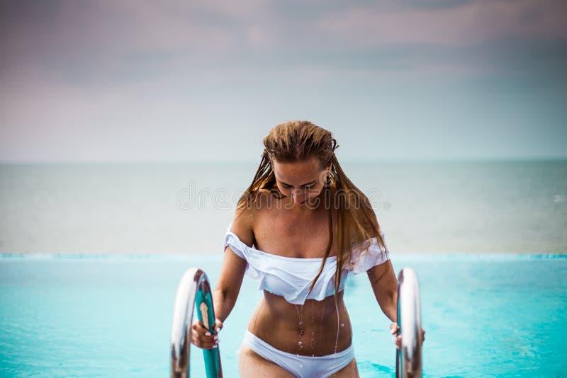 Kvinna med långt hår i swimmimgpölen med den Black Sea sikten, blå himmel, lyxig semesterort, Krim royaltyfria bilder