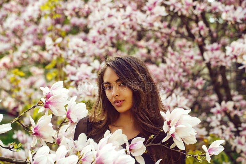 Kvinna med långt hår som poserar på att blomstra magnoliaträdet royaltyfri fotografi