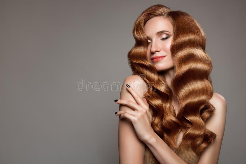 Kvinna med långt lockigt härligt ljust rödbrun hår arkivfoto