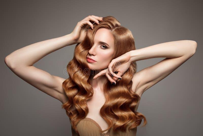 Kvinna med långt lockigt härligt ljust rödbrun hår arkivfoton