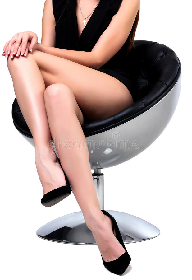 Kvinna med l?nga ben som sitter i en stol fotografering för bildbyråer