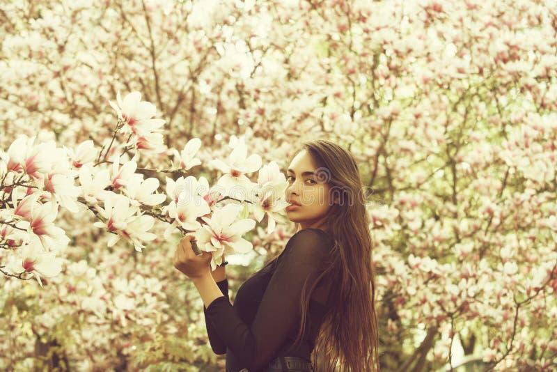 Kvinna med l?ngt, brunetth?r som poserar p? magnoliatr?det fotografering för bildbyråer