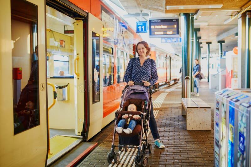 Kvinna med lilla flickan på järnvägsstationen royaltyfria foton