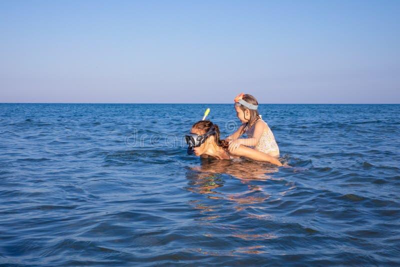 Kvinna med lilla flickan som piggybacking med att dyka exponeringsglas i vattnet av en strand i Andalusia fotografering för bildbyråer