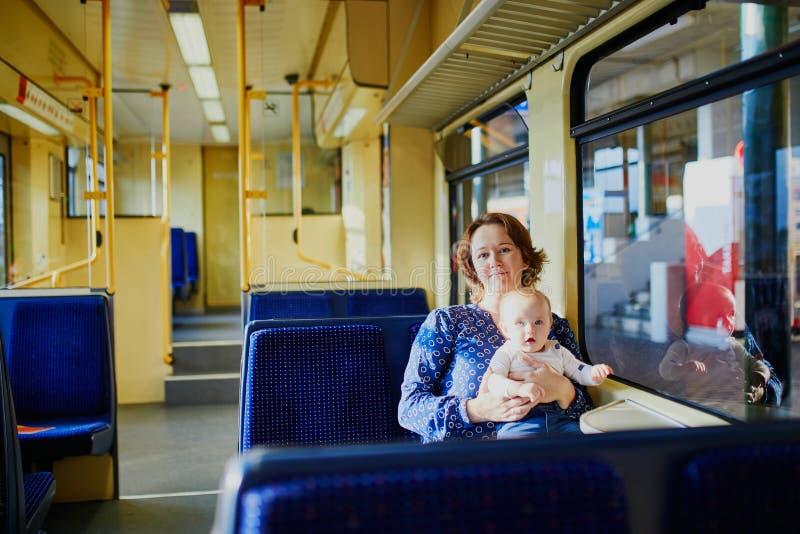 Kvinna med lilla flickan som reser med drevet royaltyfria foton