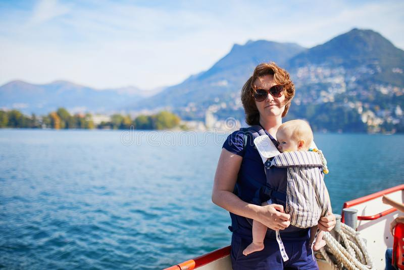 Kvinna med lilla flickan som tycker om den sceniska sikten Lugano från sjön royaltyfria foton