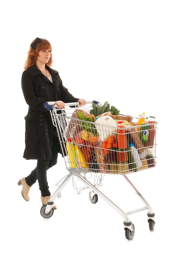 Kvinna med livsmedelsbutiken för mejeri för shoppingvagn den fulla royaltyfri bild