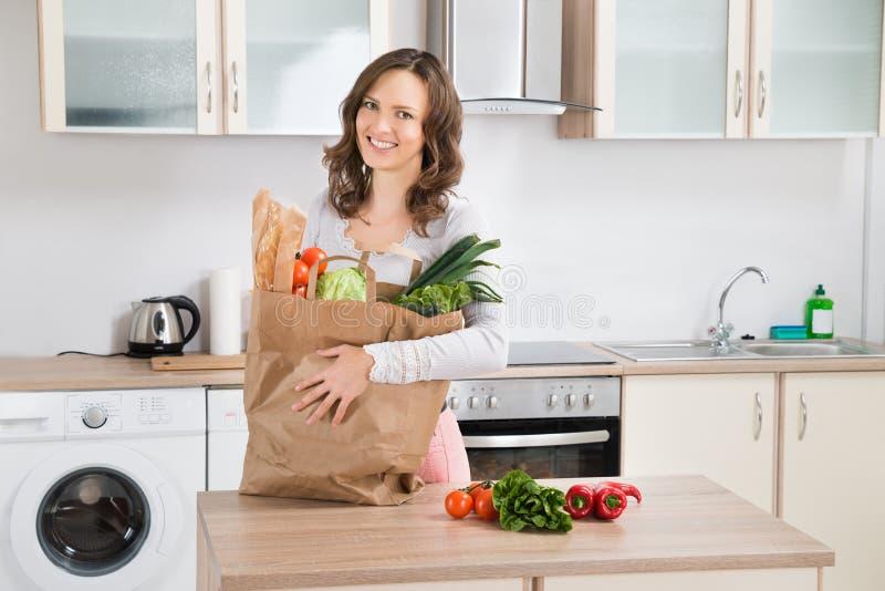 Kvinna med livsmedelsbutikpåsen i kök arkivbilder
