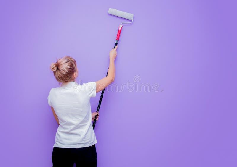 Kvinna med målarfärgrullen i eget husförsök till att måla ett rum arkivbild