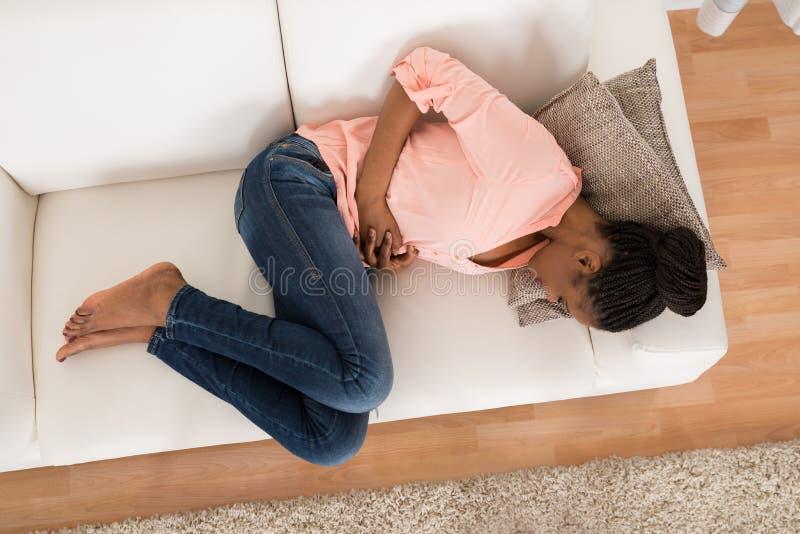 Kvinna med mageknipet som ligger på soffan fotografering för bildbyråer