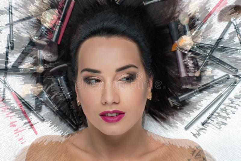 kvinna med makeup i borstarna för makeup royaltyfri bild