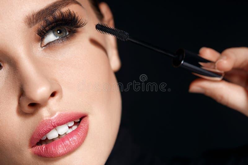 Kvinna med makeup, långa ögonfrans som applicerar mascara Göra makeup royaltyfria foton