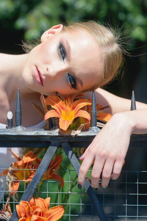 Kvinna med makeup p? sund hud med blomman arkivbilder