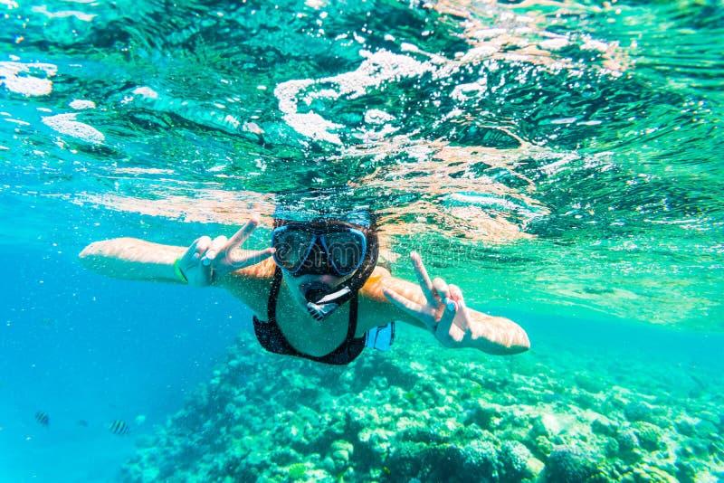Kvinna med maskeringen som snorklar i klart havsvatten med segertecknet arkivfoton