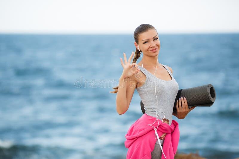 Kvinna med mattt för kondition på kusten royaltyfri fotografi