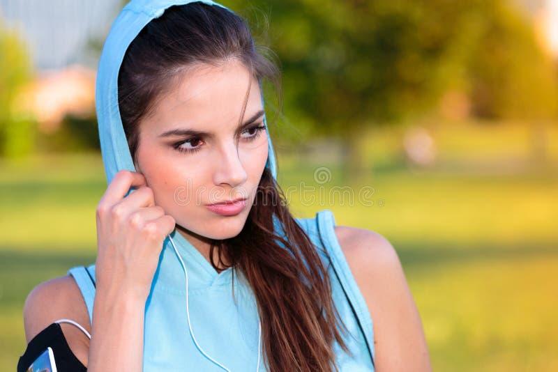 Kvinna med med huva lyssna till musik från hennes smarta telefon royaltyfri foto