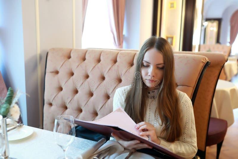 Kvinna med menyboken royaltyfri fotografi