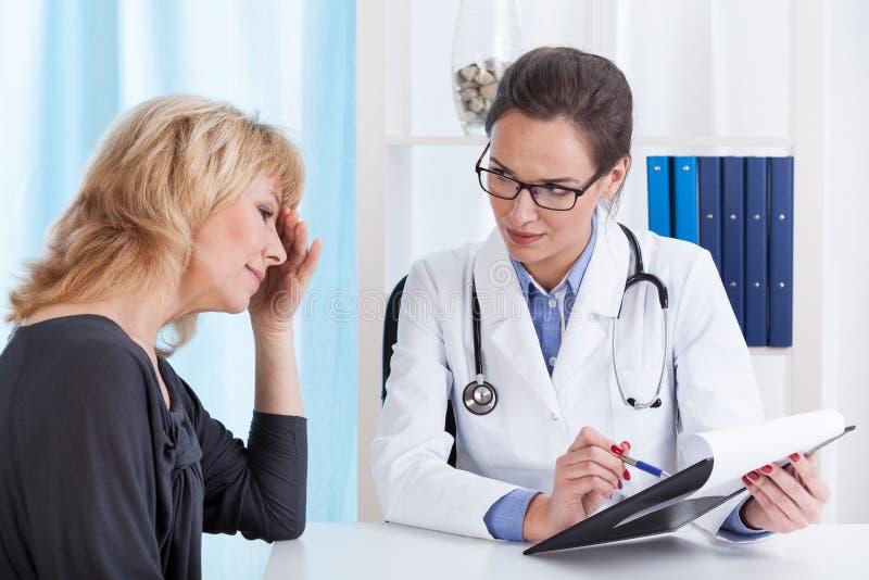 Kvinna med migrän i doktors kontor arkivbild
