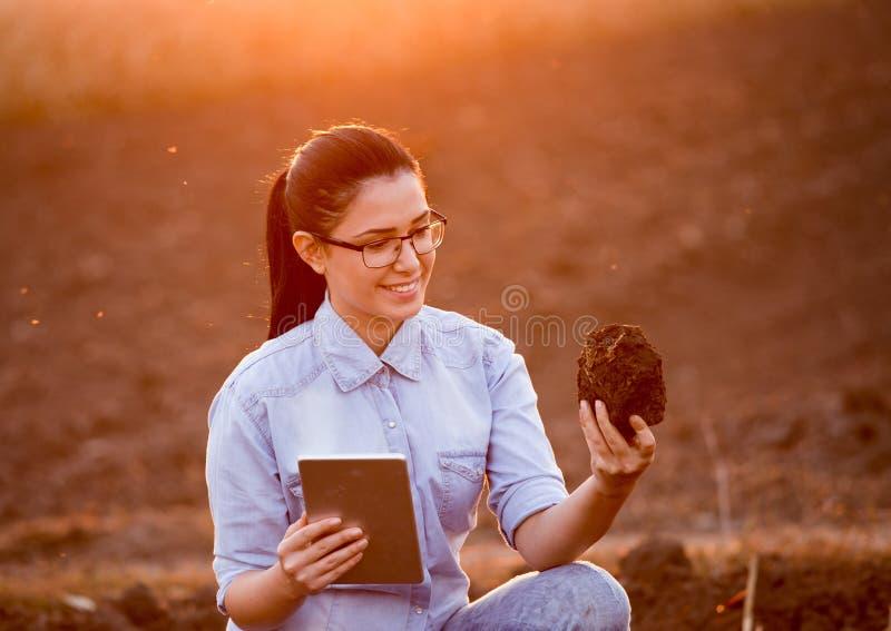 Kvinna med minnestavla- och jordklumpen royaltyfria foton