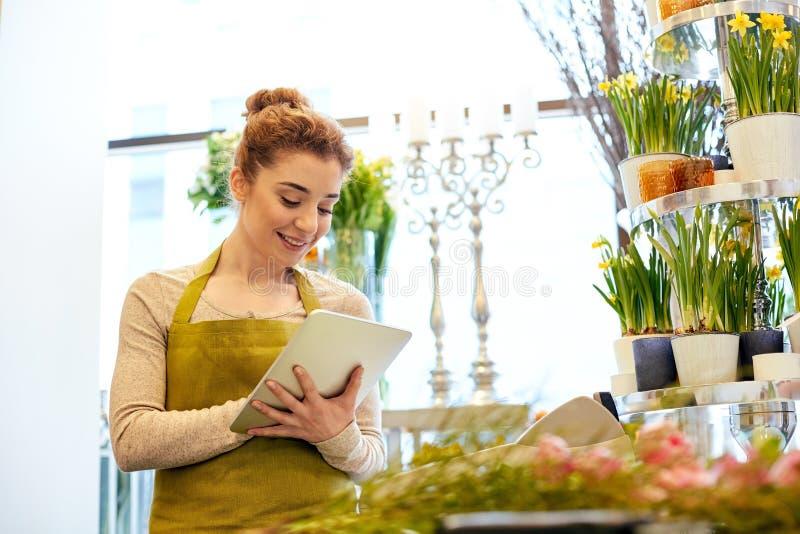 Kvinna med minnestavlaPCdatoren på blomsterhandeln arkivfoton