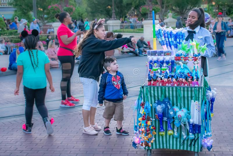 Kvinna med Minnies öron som köper hennes son en Disney leksak på det magiska kungariket arkivbilder