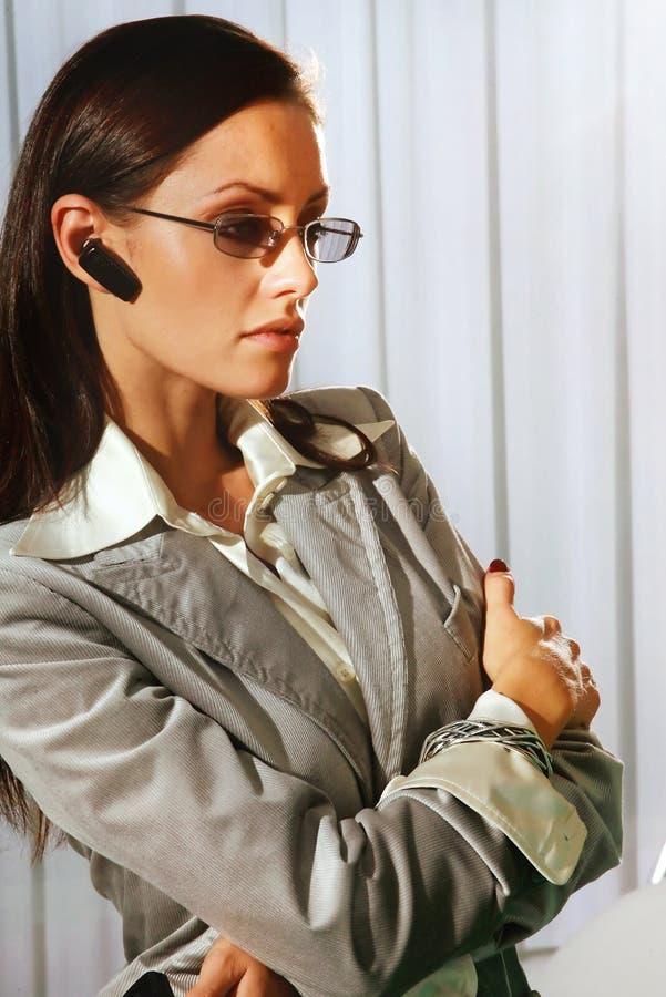 Kvinna med mobila enheten i öra royaltyfri bild