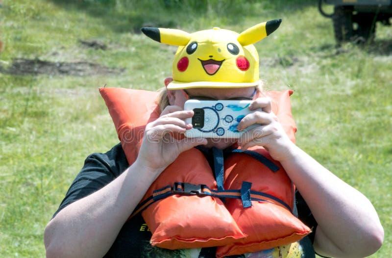 Kvinna med mobiltelefonen och den roliga hatten royaltyfri fotografi