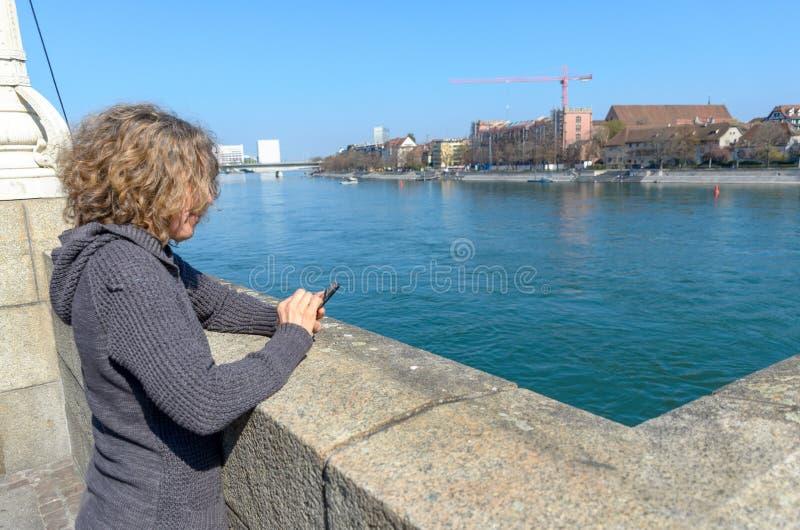 Kvinna med mobiltelefonen på invallningen royaltyfri fotografi