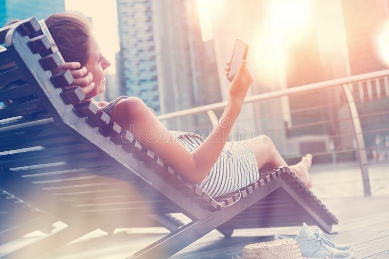 Kvinna med mobiltelefonen som vilar på solstol och lyssnande musik nära centrum royaltyfria foton