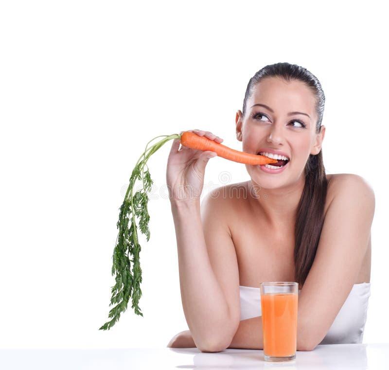 Kvinna med morotfruktsaften royaltyfria bilder