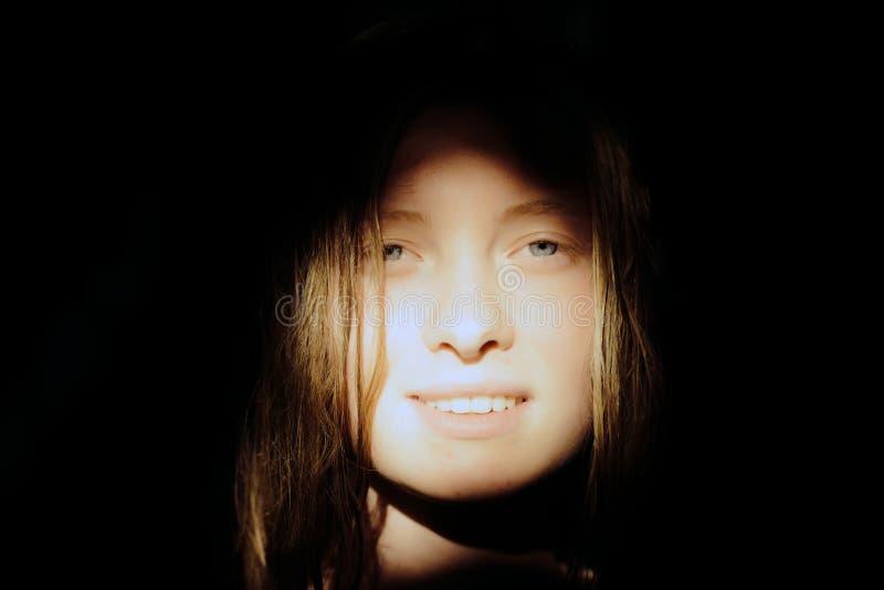 Kvinna med n?tt framsidaleende i soligt ljus Sinnlig kvinna med blont l?ngt h?r p? m?rk bakgrund Sk?nhetmodell med inte royaltyfri fotografi