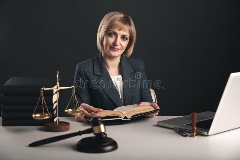 Kvinna med notarius publicuböcker i regeringsställning Träauktionsklubba med libra- och bärbar datorbegrepp royaltyfria bilder