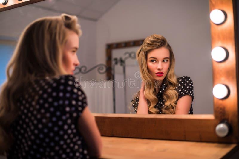 Kvinna med ny frisyrblick i spegel i skönhetsalong royaltyfria bilder
