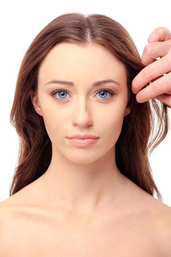Kvinna med omsorg för hand för frisör` s om hennes långa hår royaltyfri fotografi