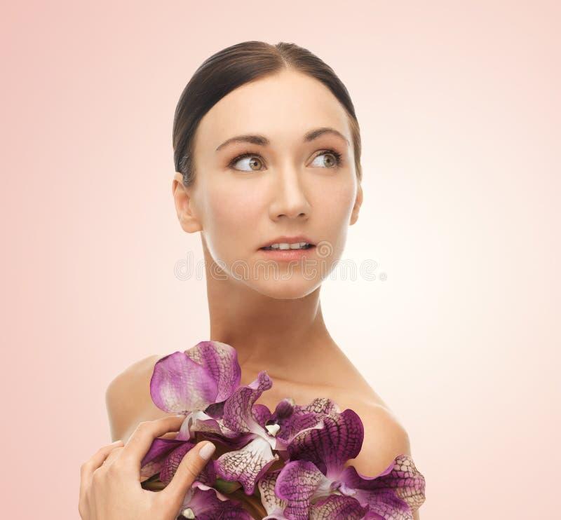Kvinna med orhidblommor royaltyfri bild