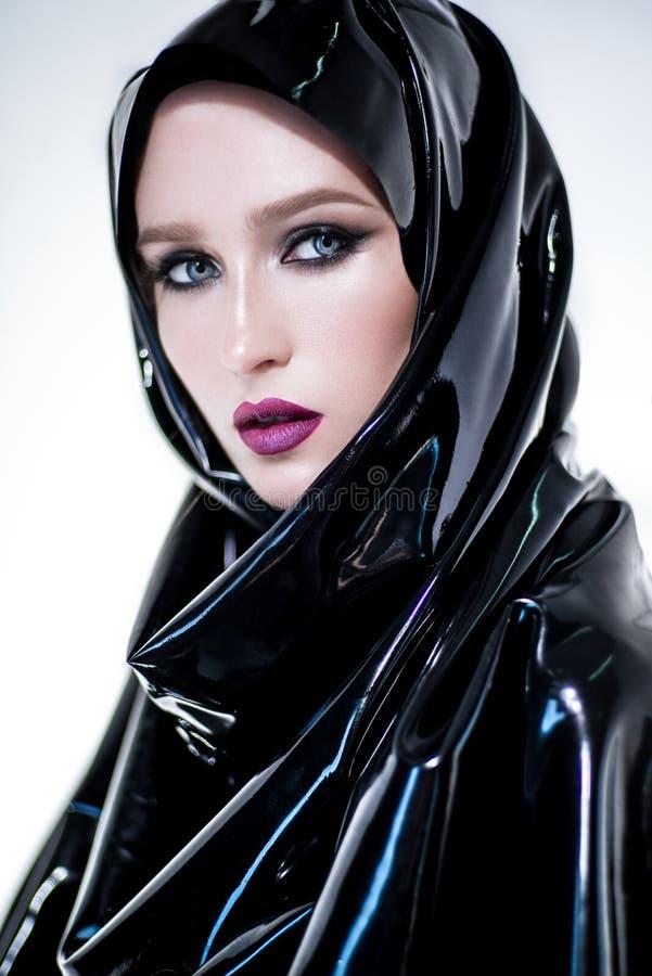Kvinna med orientalisk makeup- och svartlatexhijab arkivbild