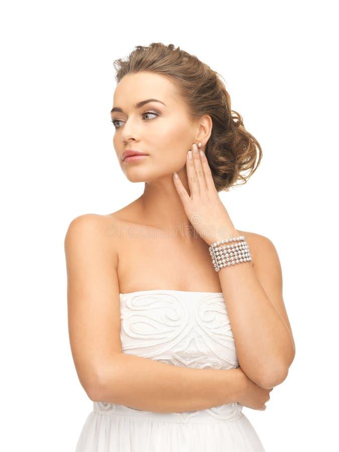 Kvinna med pärlemorfärg örhängen och armbandet fotografering för bildbyråer