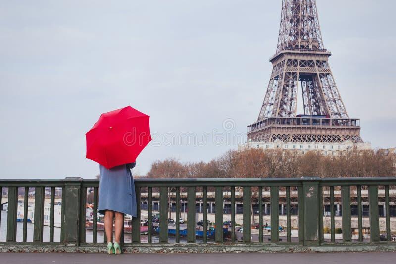 Kvinna med paraplyet som ser Eiffeltorn i Paris, lopp till Frankrike royaltyfria bilder