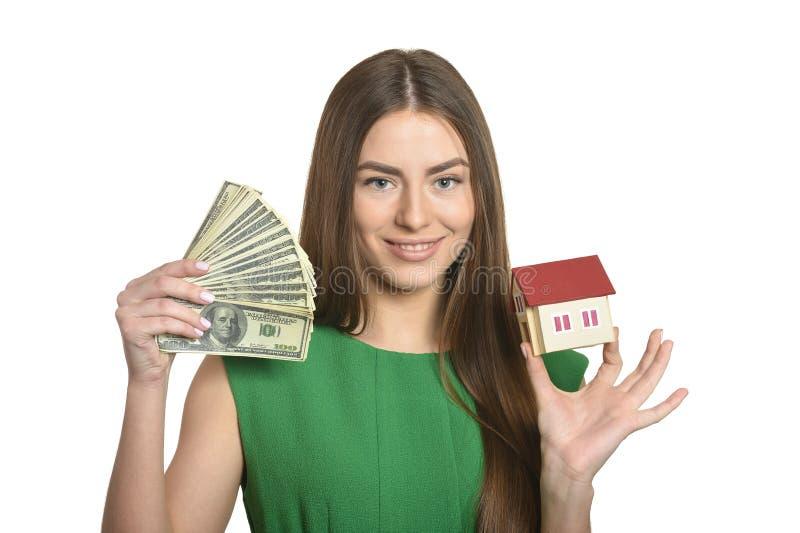 Kvinna med pengar och det lilla huset royaltyfri foto