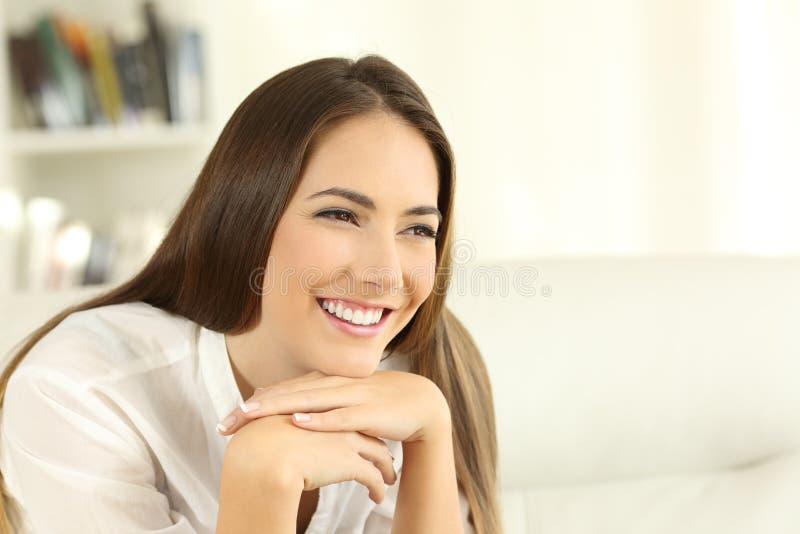 Kvinna med perfekta tänder som hemma ler royaltyfri foto