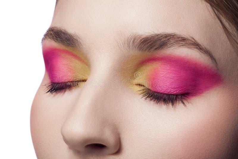 Kvinna med röda och gula den isolerade makeupcloseupståenden royaltyfri fotografi