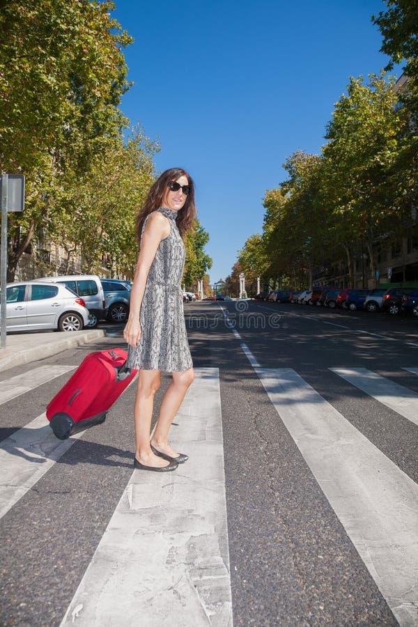 Kvinna med resväskan i övergångsställe arkivfoton