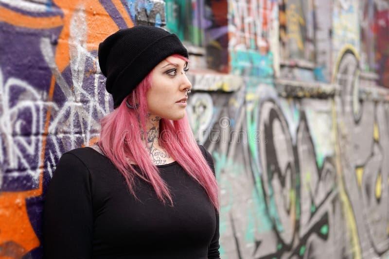 Kvinna med rosa hårpiercingar och tatueringar som lutar mot grafittiväggen royaltyfri foto