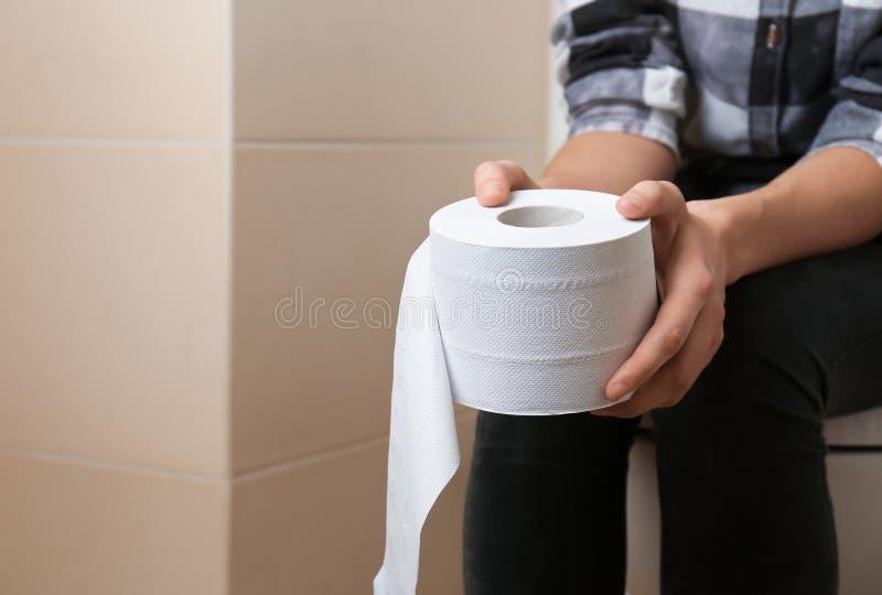 Kvinna med rulle av papper som sitter på toalettbunken i toalett royaltyfri foto