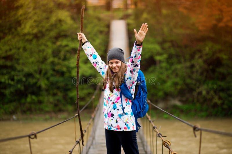 Kvinna med ryggsäcken och händer upp att fotvandra skogen för livsstilaffärsföretagbegrepp och den arga floden i aktiva semestrar royaltyfri bild