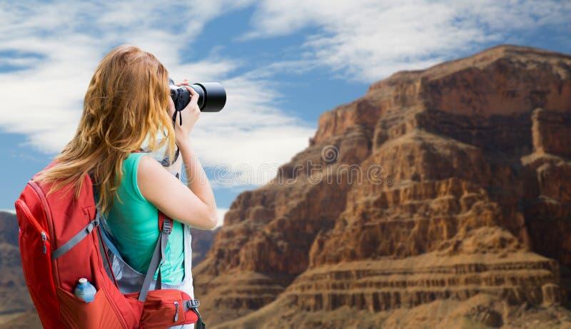 Kvinna med ryggsäcken och kamera på Grandet Canyon arkivbilder
