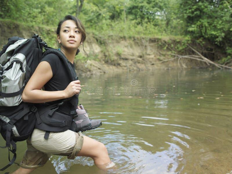 Kvinna med ryggsäcken som går i Forest Water arkivbild