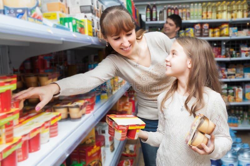 Kvinna med söta yoghurter för dotterköpande arkivfoto
