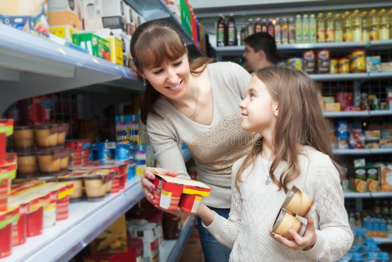 Kvinna med söta yoghurter för dotterköpande arkivbilder