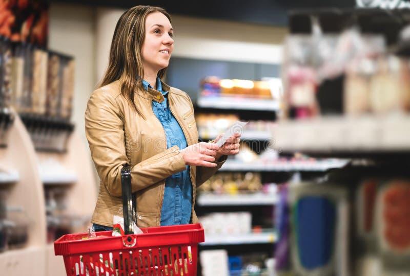 Kvinna med shoppinglistan i supermarket och livsmedelsbutik royaltyfri bild